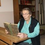 Frau Rademacher liest interessiert in einem alten Buch. (Foto: SMMP/Büker)